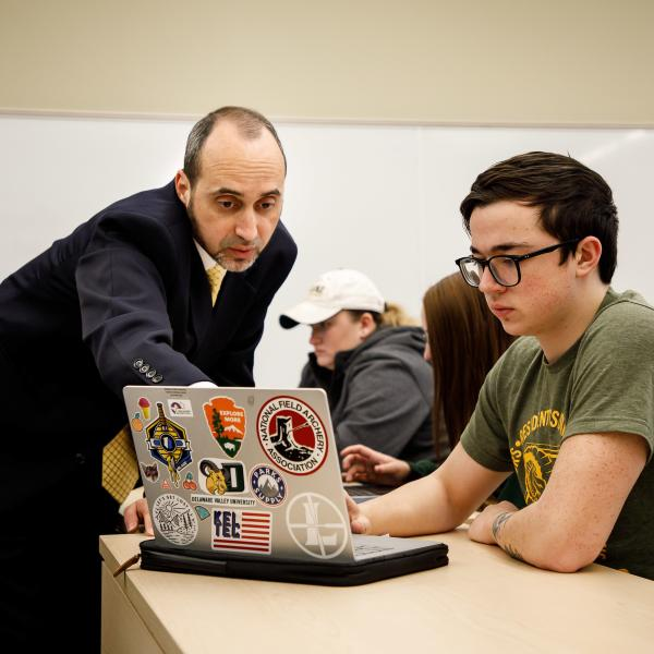 A professor and a student reviewing work on a laptop.