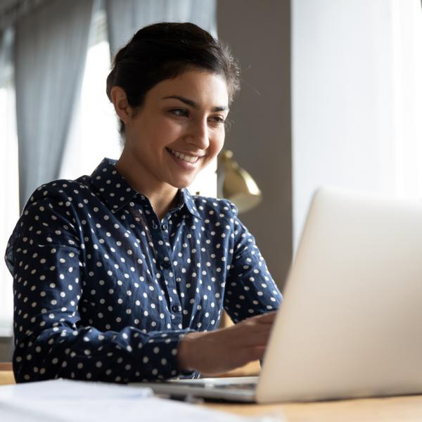 Young woman smiling looking at a laptop.