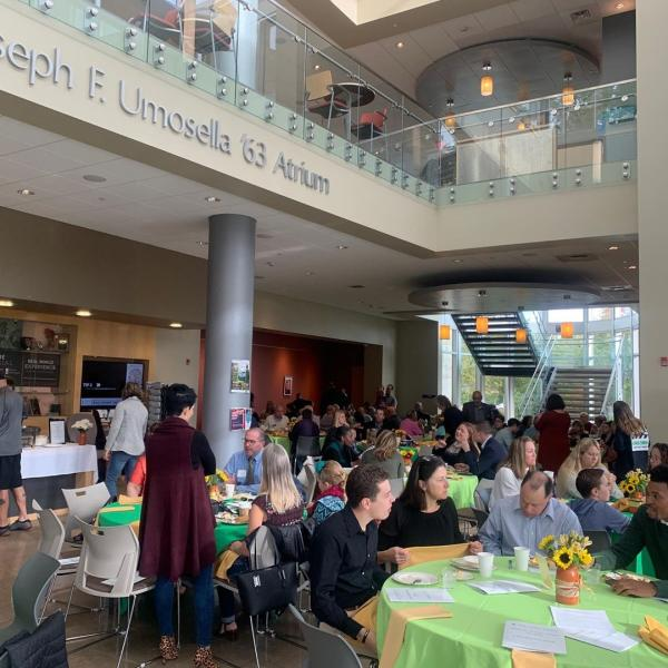 Alumni seated in the atrium at round tables.