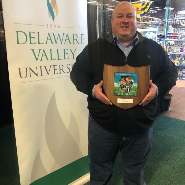 A man stands next to a DelVal banner with a plaque that recognizes the best booth at the PA Farm Show
