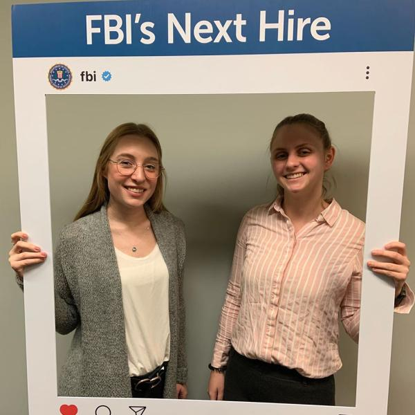 "Two female students in a frame saying ""FBI's next hire"" at the top."