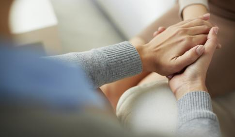 Two people hold hands in a counseling or support meeting.