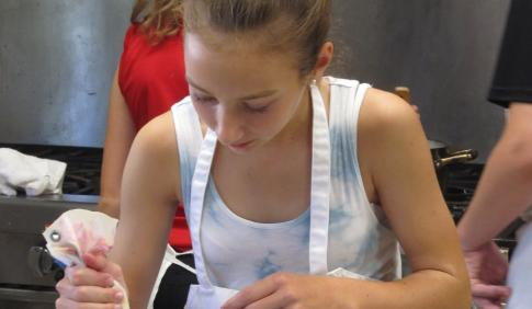 A young girl works with a piping bag.
