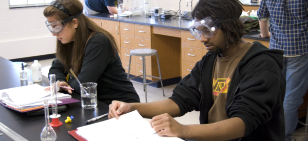 Students wearing safety goggles in a biology laboratory.