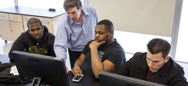 3 college-aged students and a professor having a discussion and looking a at a computer