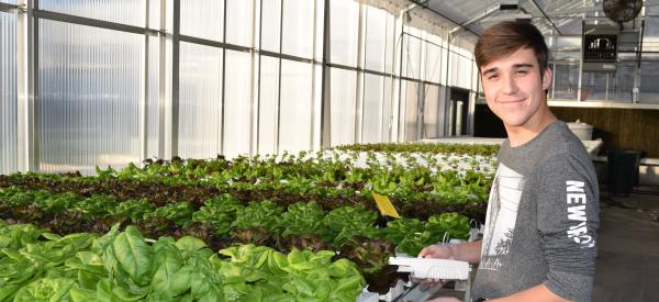 A smiling male student doing research in a greenhouse surrounded by plants