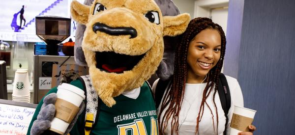 A student holds a Starbucks coffee and stands with the Delaware Valley University mascot who is also holding a Starbucks coffee.