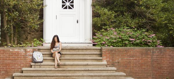 Student reading book on stairs in front of the chapel