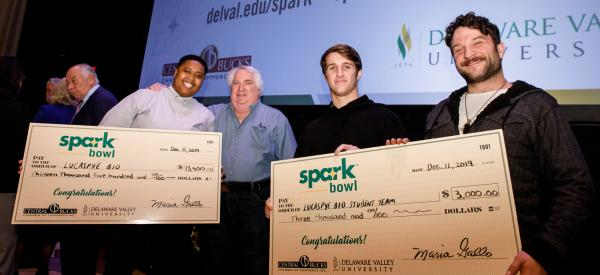 Students winners proudly displaying their checks
