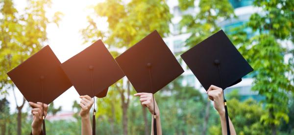 Four graduation caps being head up by their corners.