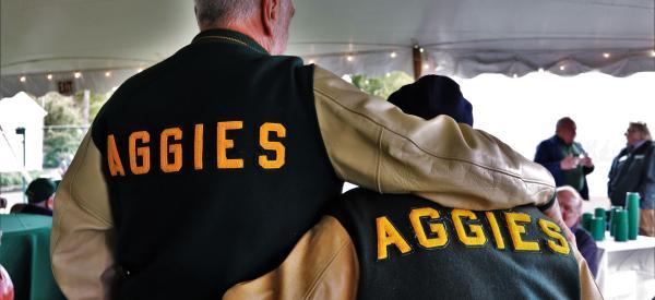 Two alumni embrasing wearing Aggies leterman jackets